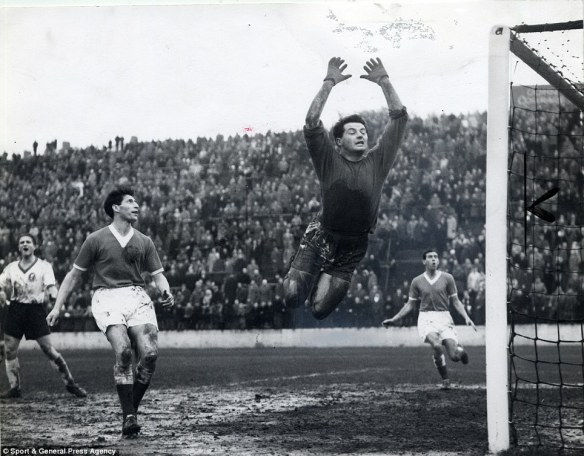 Charlton Athletic beating Liverpool FC 3-0 (yes, honestly), The Valley, December 1959. Charlton Goalie, Willie Duff, scrambles to clear some smudges from the photo.  Not a dry hat in the house.